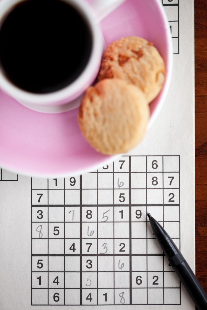 A cup of coffee and biscotti sitting on a pink plate near a Sudoku puzzle to celebrate National Puzzle Day.