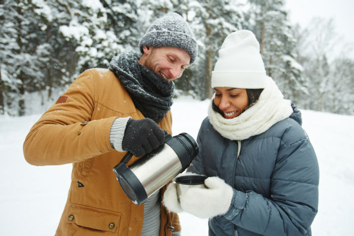 Man and woman on cold weather gear sharing a thermos.