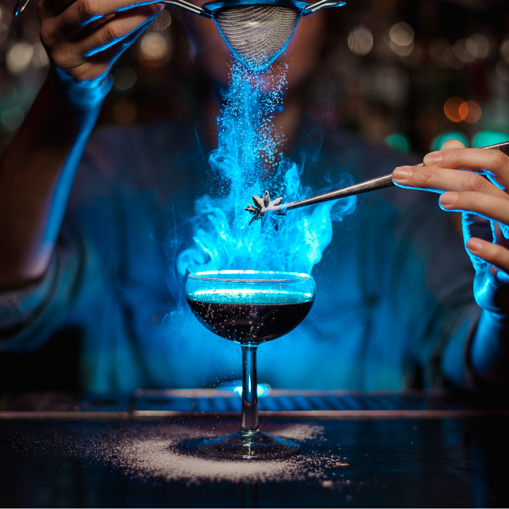 Bartender making a blue cocktail lit on fire to celebrate fun bartending facts.