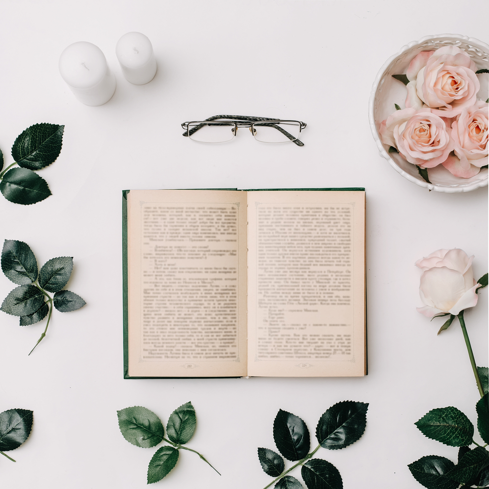 An open book on a white background with roses and two candles.