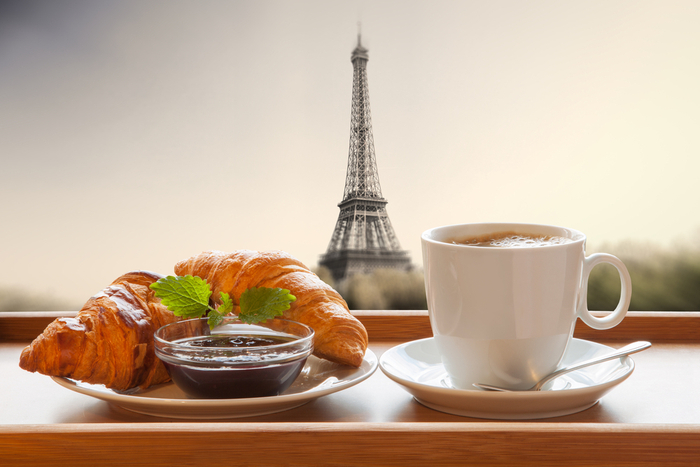 A cafe au lait and croissant with the Eiffel Tower in the background to celebrate the cafe au lait meaning.