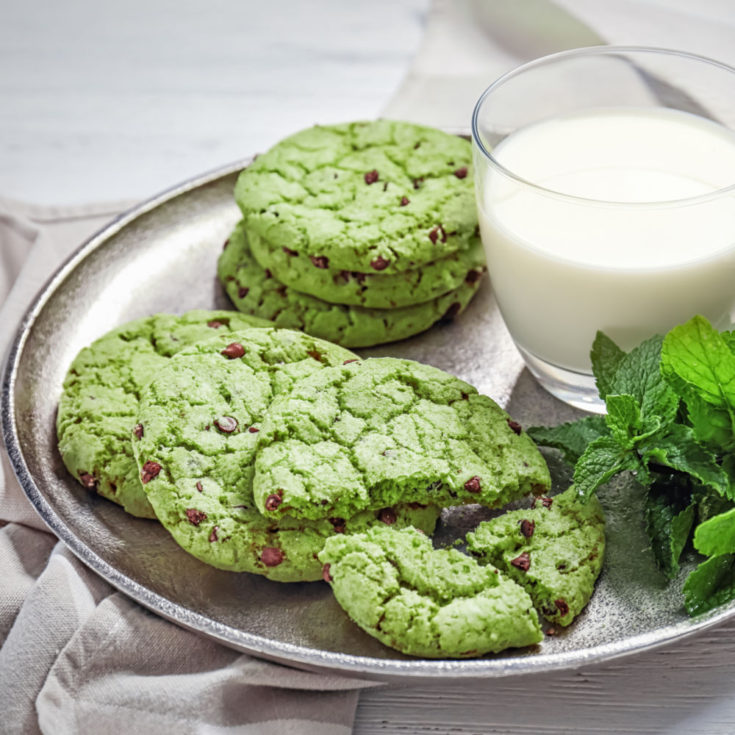 Mint chocolate chip cookies on a plate with a glass of mink.