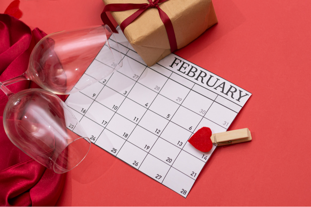 A February calendar of national days on a red background with wine glasses, a present and a heart around it.