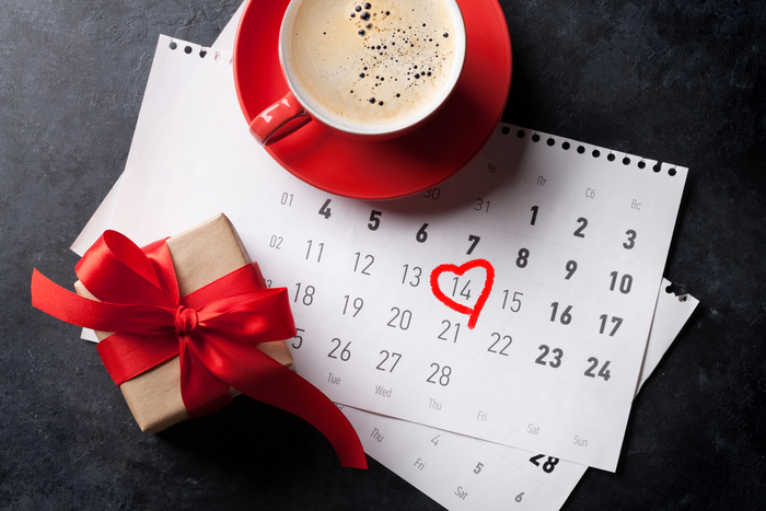 Hot chocolate and a wrapped present on a national days in February calendar with Valentine's Day circled.