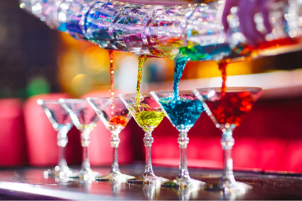A line of martini glasses being filled with different color cocktails on a bar by a flair bartender.