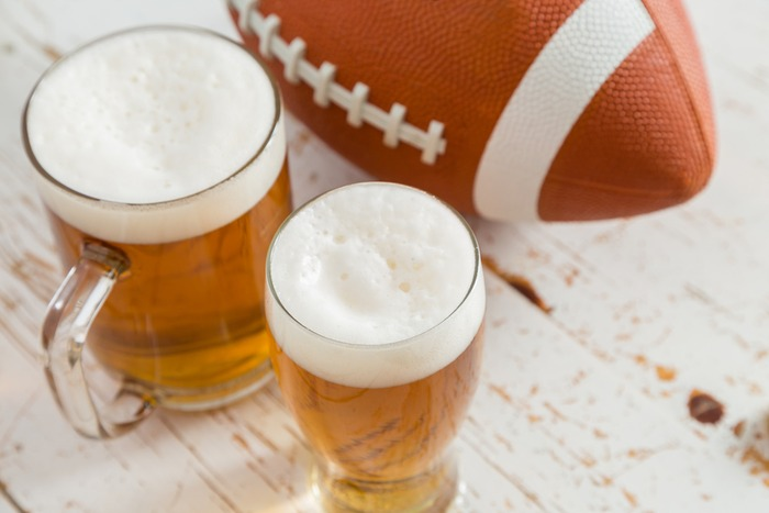 Football and two beers on a white distressed table on National Football Hangover Day.