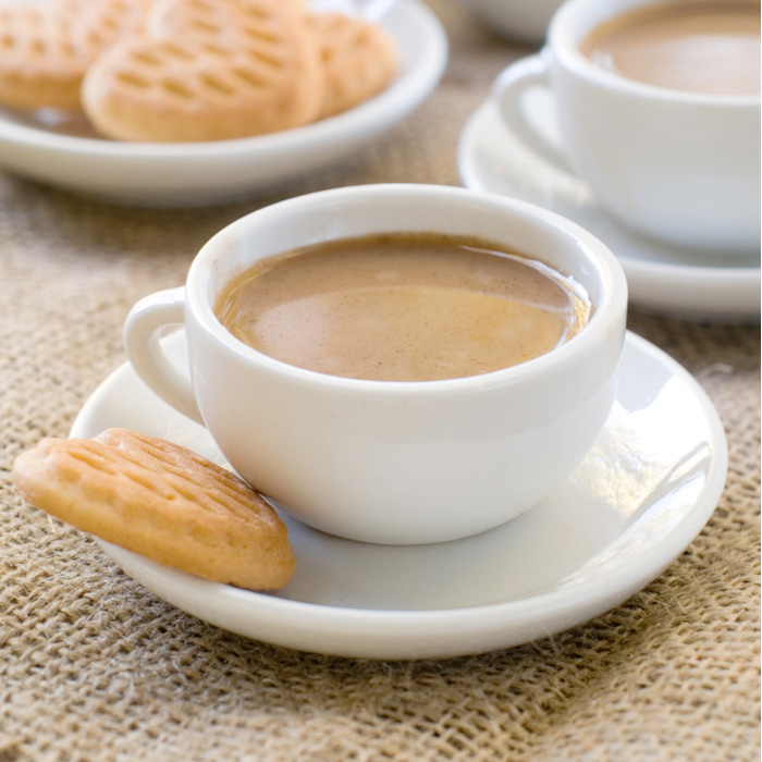 A cafe au lait and biscotti on burlap to celebrate National Cafe Au Lait Day.