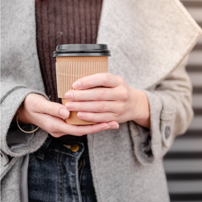 A woman holding a to go coffee cup after learning how to make a cafe au lait.