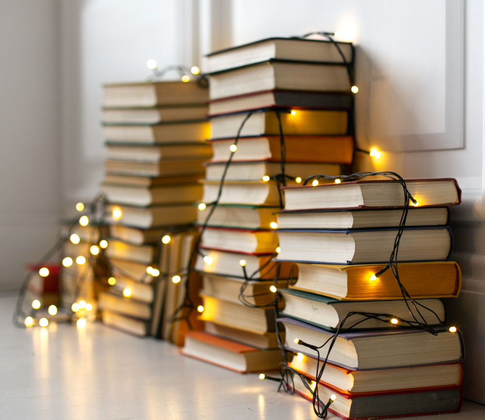 Four piles of books with twinkle lights draped over them.