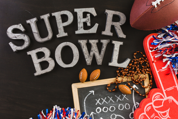 A flatlay of football fan paraphernalia and letters spelling out Super Bowl (showing that Super Bowl is two words).