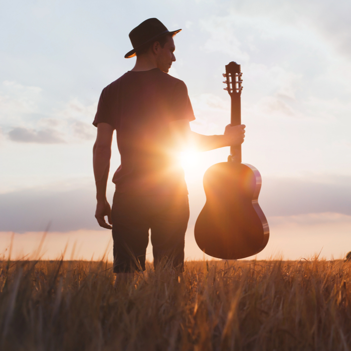 Man with a hat holding a guitar at sunset in a field on Get Out Your Guitar Day.