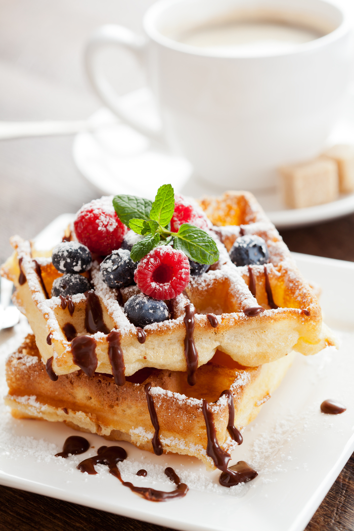 A stack of waffles in front of a latte to celebrate Galentine's Day.