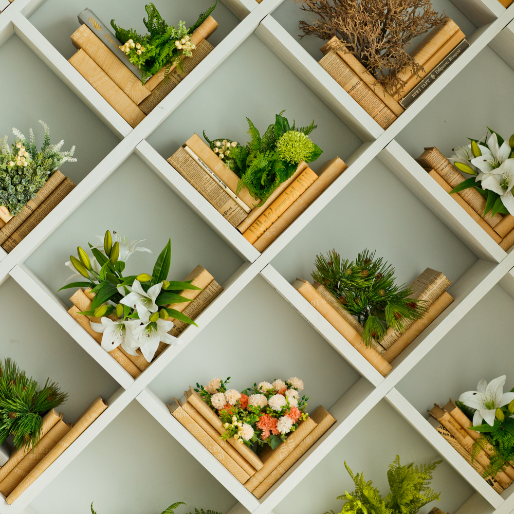 An image of styled bookshelves with tan colored books laying diagonally with plants on top of them.