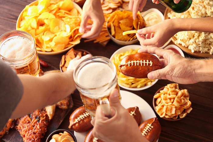 Hands holding beer and digging into appetizers for a party about football.