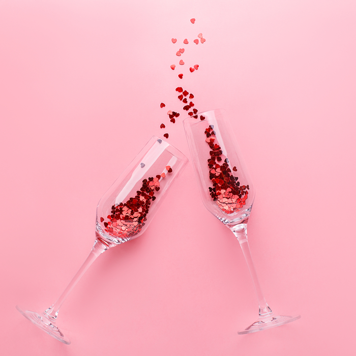 Two champagne flutes toasting with pink glitter to celebrate what is Galentine's Day.