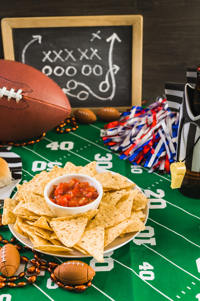 a table with a chalk board, football, and snacks on it.
