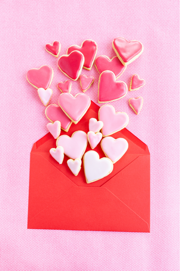 A red envelope with heart shaped cookies coming out of it to celebrate when is Galentine's Day.
