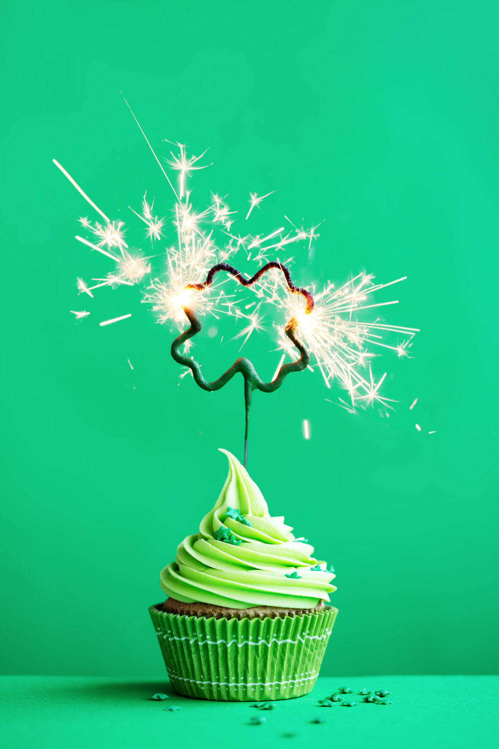 A cupcake with green icing and a sparkler in the shape of a shamrock to wish everyone a happy St. Patrick's Day.