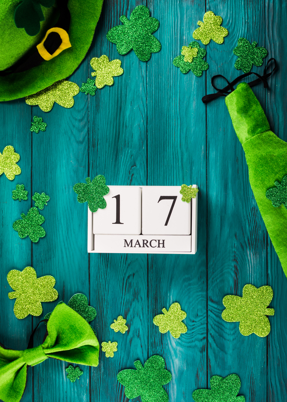 March 17 blocks, glittery shamrocks and a green hat on a table to celebrate the date of St. Patrick's Day.