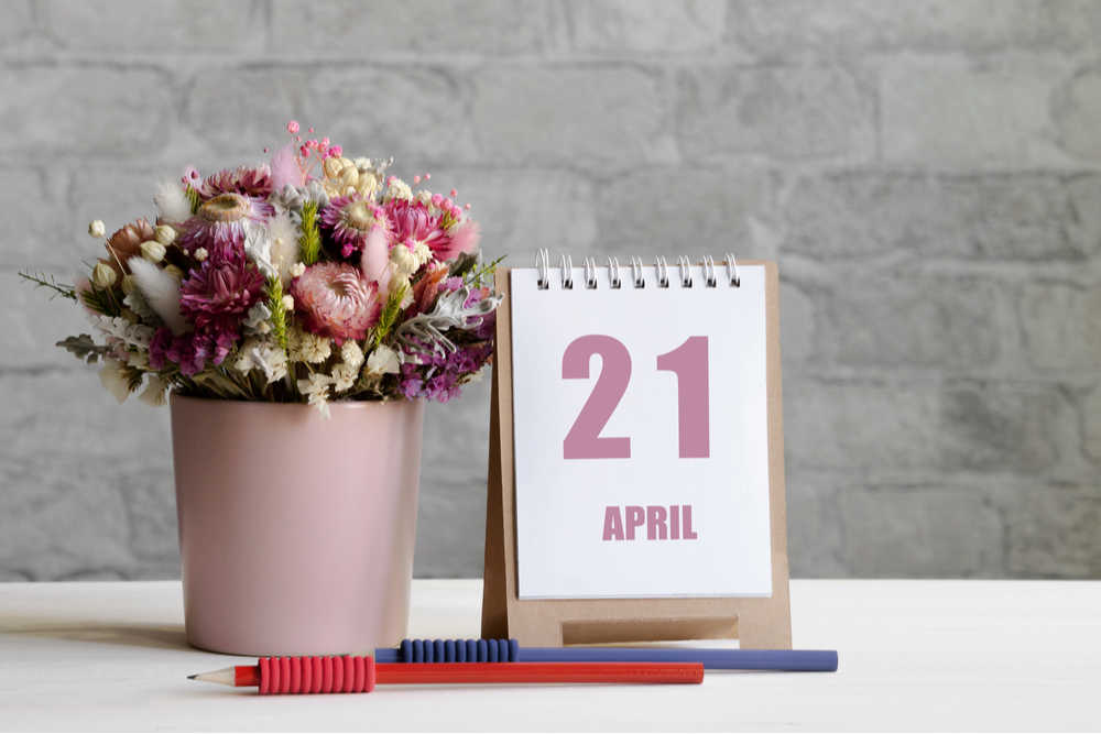 A vase of cut flowers next to a calendar that says April 21, to celebrate the April 21 national days.