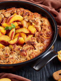 A photo of a peach cobbler recipe made in a cast iron pan, with a red cloth and peaches styled around it.