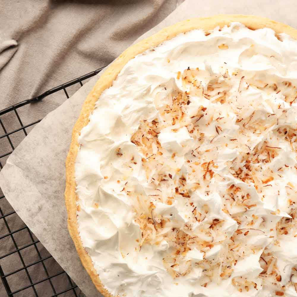 A coconut cream pie on a drying rack with parchment paper under it next to a blanket.