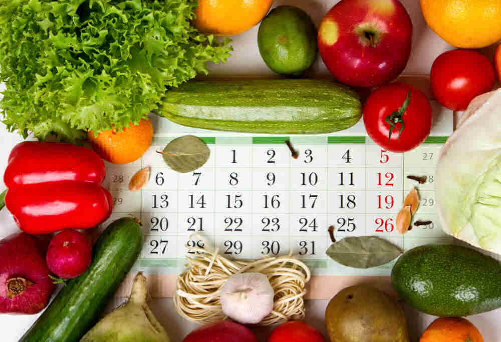 Fresh fruit and vegetables surrounding a calendar page.
