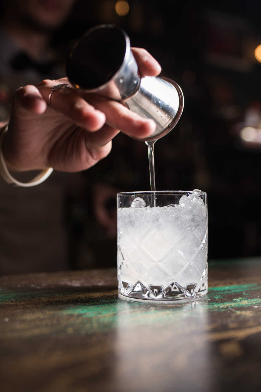 A bartender pouring vodka into a short glass over ice using a jigger for National Vodka Day.