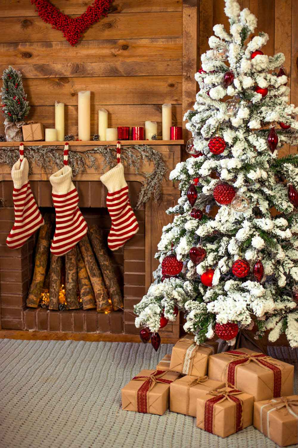 A cozy living room with a flocked tree, a fire filled with wood, three striped stockings and candles on the mantle.