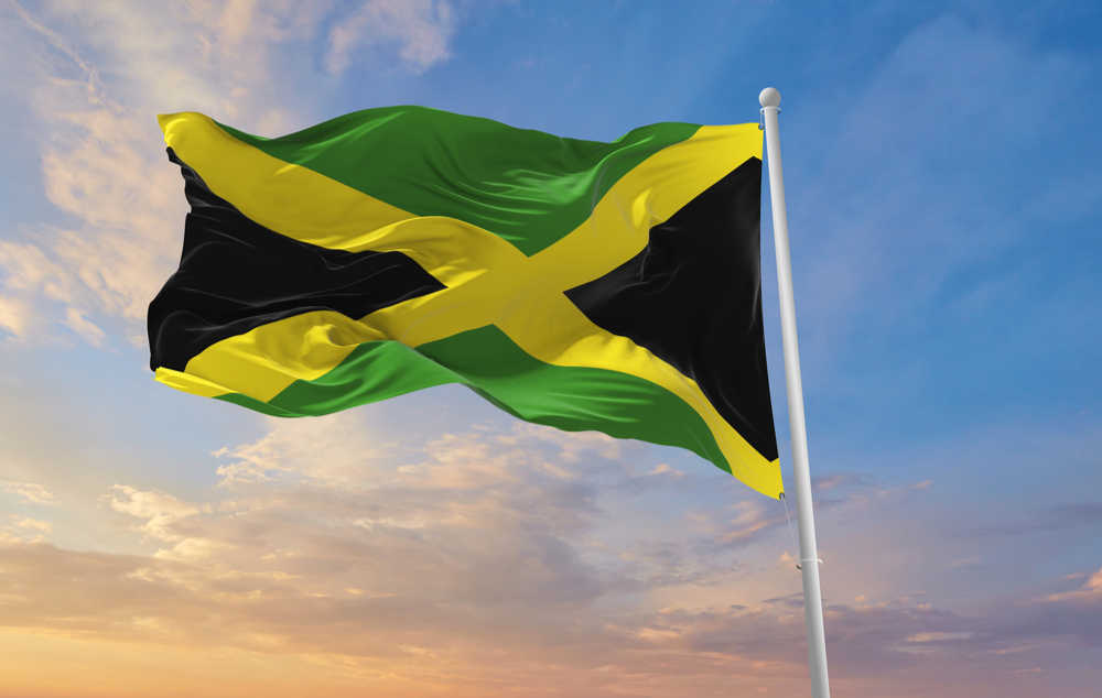 A Jamaican flag waving in the wind in front of a a sunset.