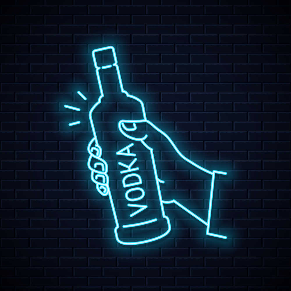 """A neon sign of a hand holding a bottle with the word """"vodka"""" written on it vertically."""