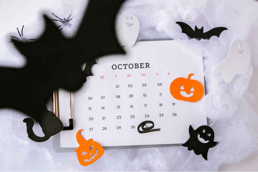 A spooky October calendar surrounded by cutout shapes of pumpkins, ghosts and bats to promote October national days.