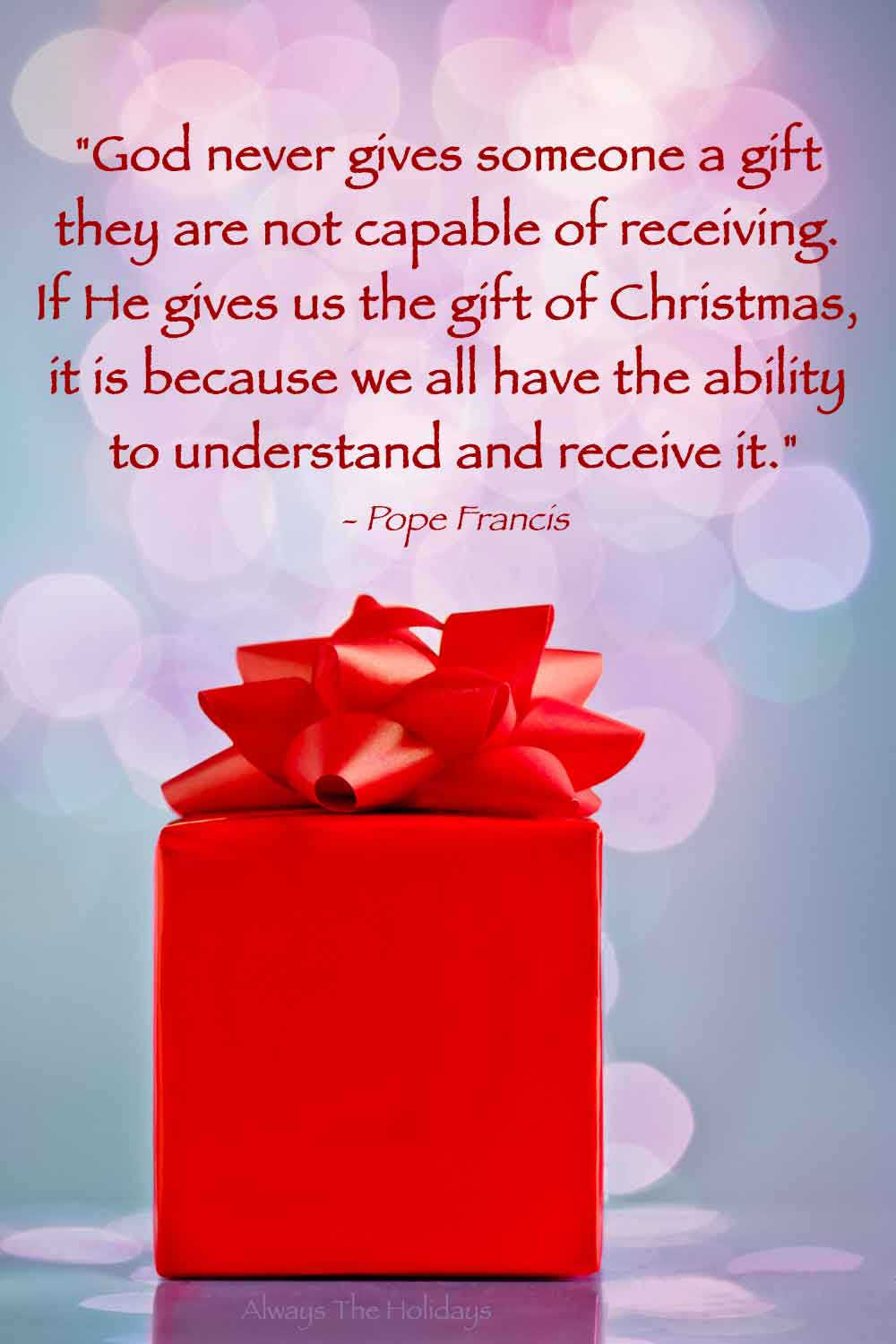 A red Christmas present in front of a pink bokeh with a text overlay containing a religious Christmas quotes about God on it.