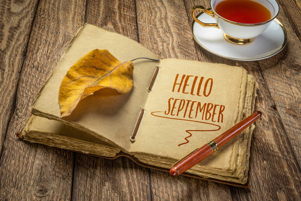 """An old journal with the words """"Hello September"""" written on it next to a cup of tea."""