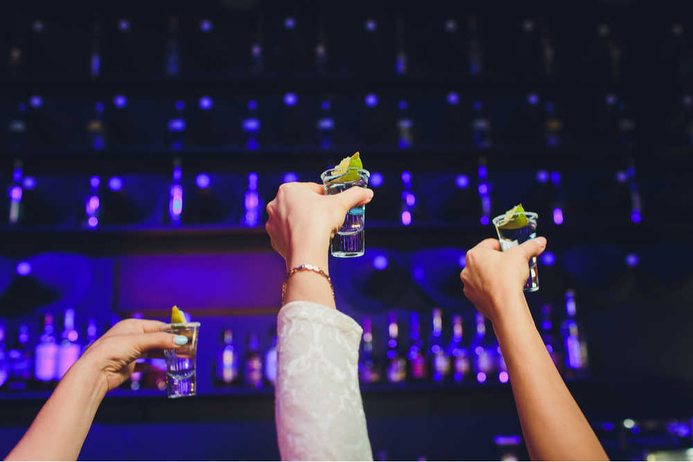 Three hands holding shots of vodka with limes balanced on top up to the sky in a cheers motion in front of a bar with purple lighting.