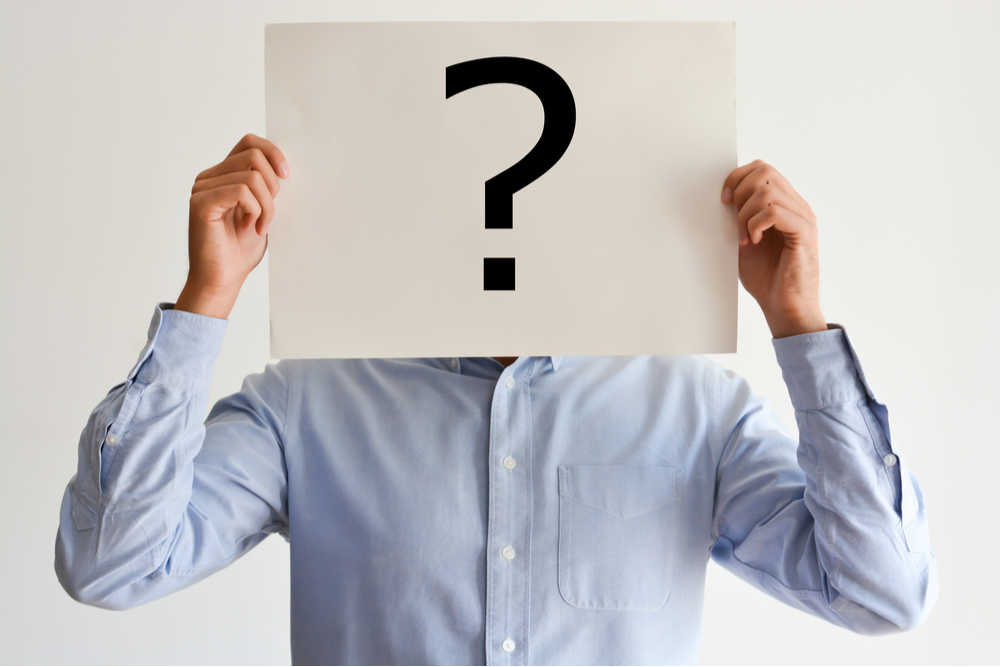 A man in a blue button down shirt holding a white piece of paper in front of his face with a question mark on it.