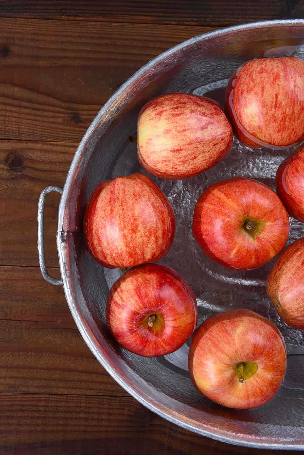A silver basin of red apples in water.