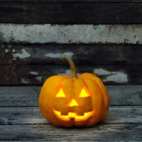 A small lit up jack o lantern against a wall that has light grey and dark grey wooden boards.