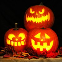 Three pumpkins with classic jack o lantern faces carved into them.