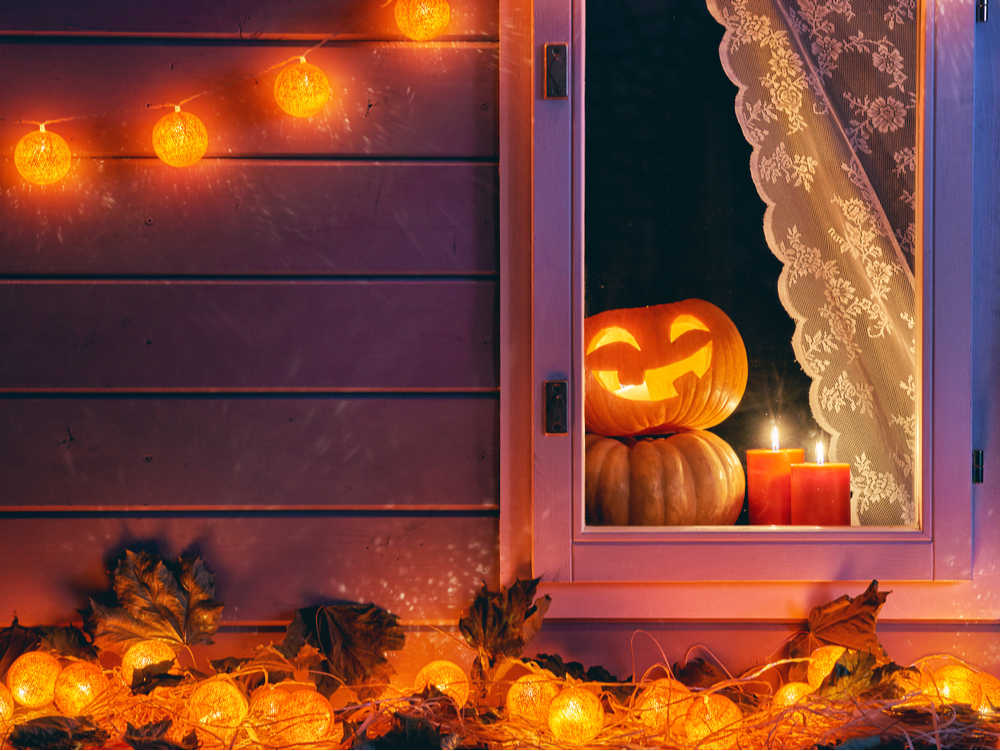A window with a jack-o-lantern peeking out from behind a lace curtain, with leaves outside the window, and a Halloween themed set of twinkle lights.