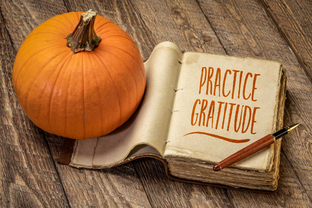 """A pumpkin and journal with the words """"practice gratitude"""" on it, on a wooden tabletop."""