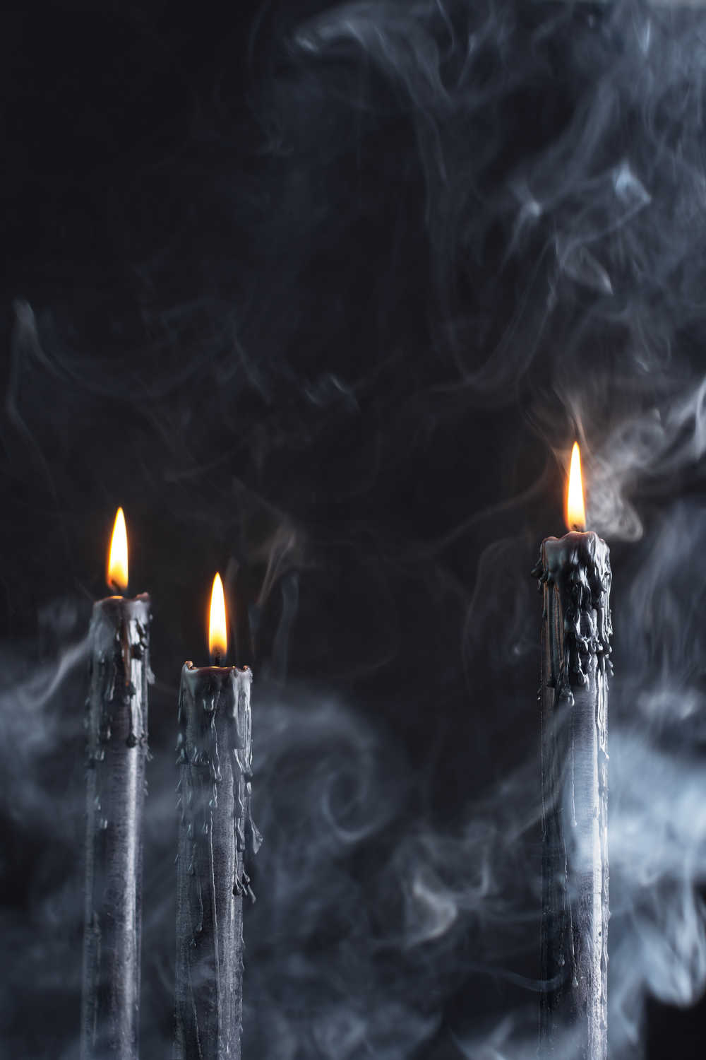 Three black candles lit against a black background with smoke and fog in the foreground.