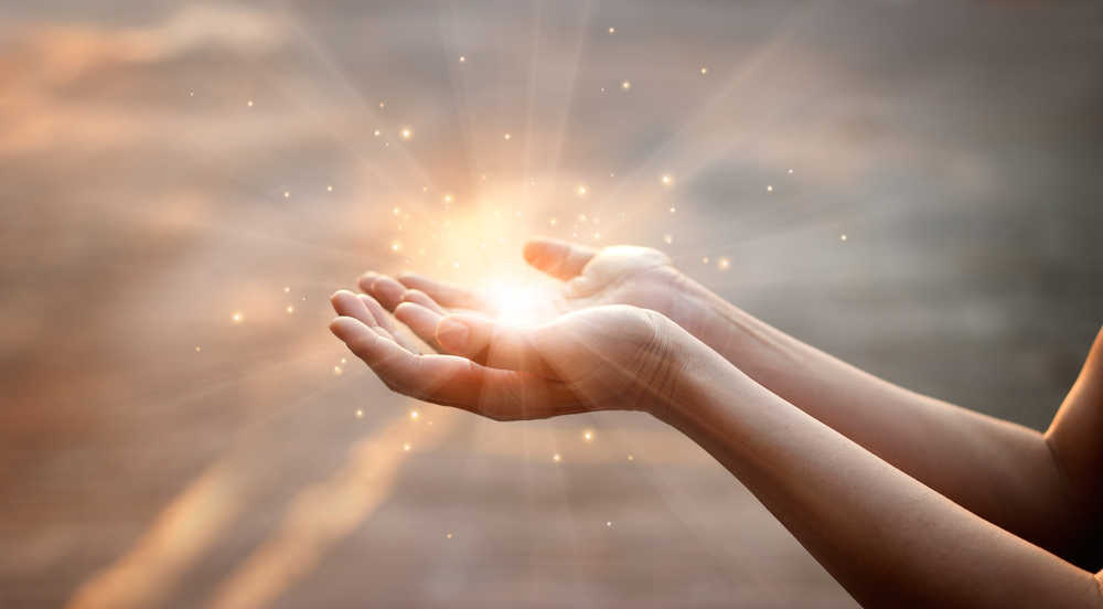 Two hands turned up to the heavens with a bright light of prayer in them.