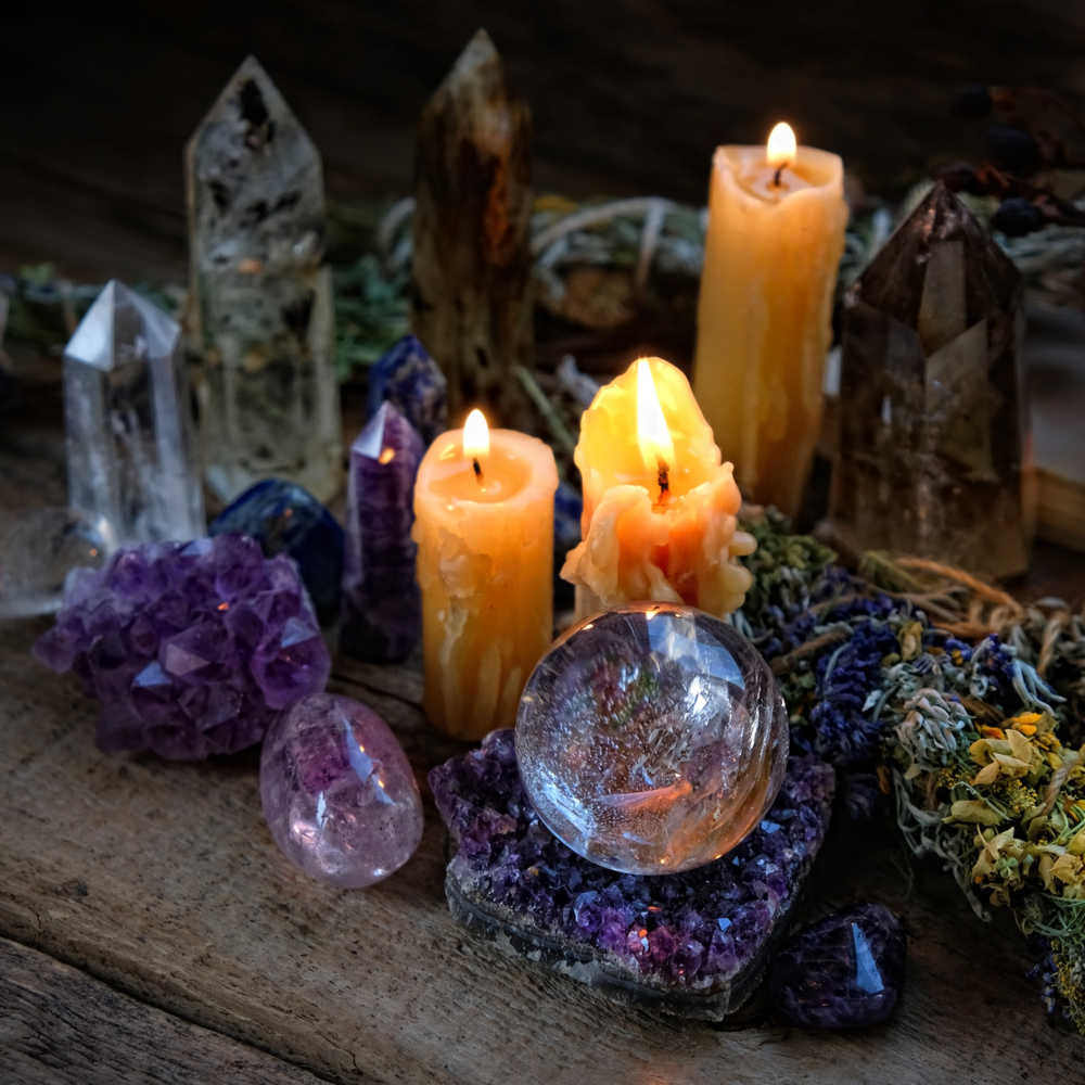 A halloween altar with candles, crystals, a sphere, and natural grassy elements that are all part of a Halloween ritual.