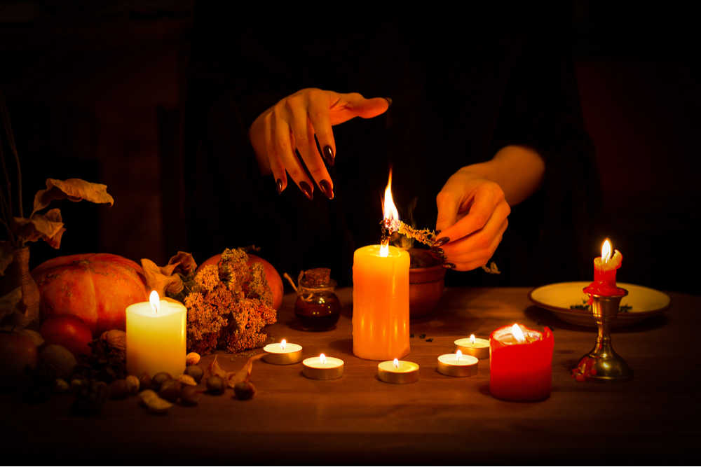 A woman with black nails lighting a large candle in the center of a semi circle of smaller lit candles as part of a Halloween tradition.