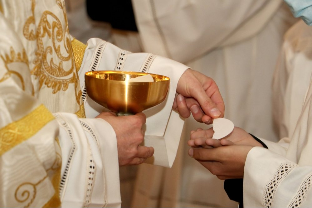 A Catholic priest offering a person Eucharist during Mass on All Saints' Day.