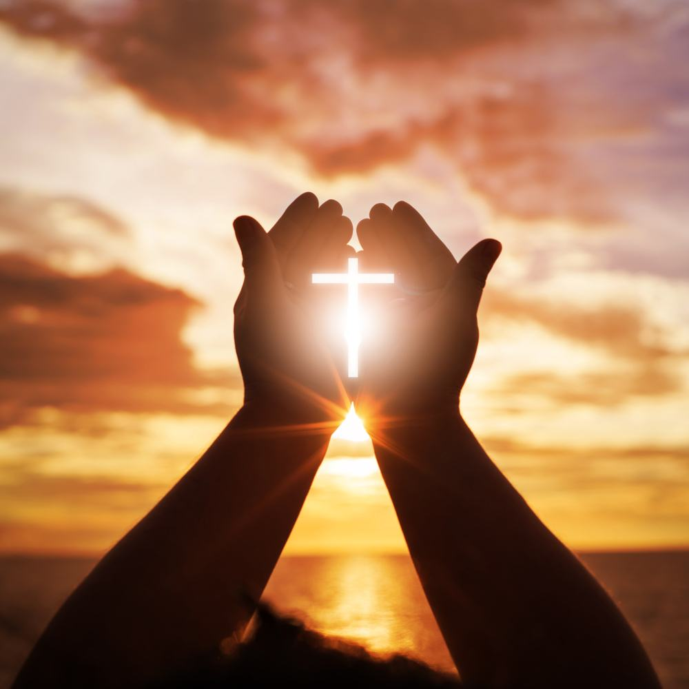 Two hands up towards an orange and yellow sky, holding a cross made out of bright white light.