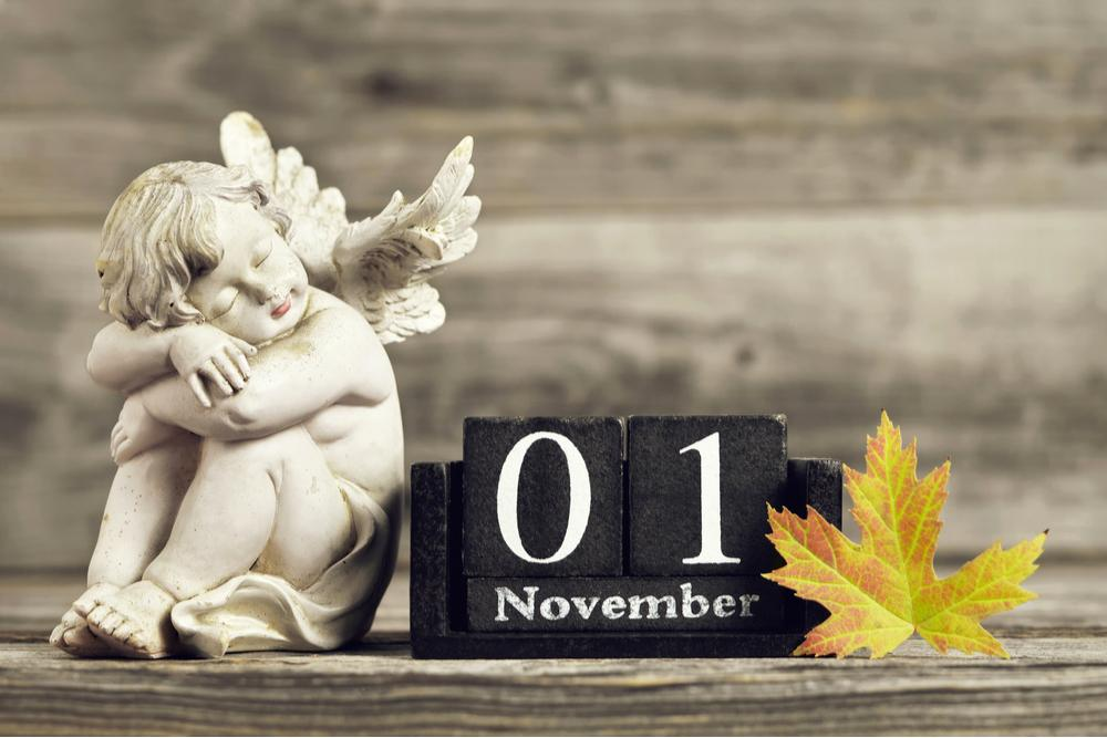 """Black blocks that read """"November 1"""" in between an angel statue and a yellow leaf."""