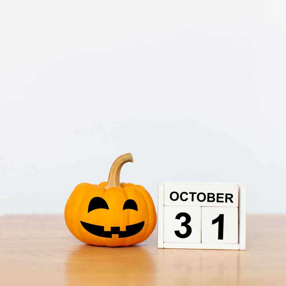 Blocks that say October 31 next to a pumpkin with a black felt smile and eyes.