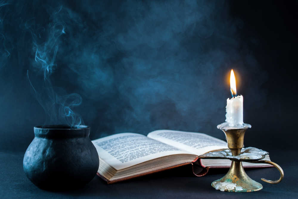 A cauldron, book about the origin of Halloween, and a lit candle against a black background laid out as the start of a Halloween ritual.